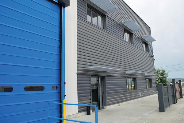 A droite, le nouveau bâtiment abritant le centre technique à l'étage, et le show-room au rez-de-chaussée. © V&MA